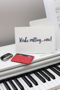 red red arrows cardholder on piano with car key fob and reds rolling card