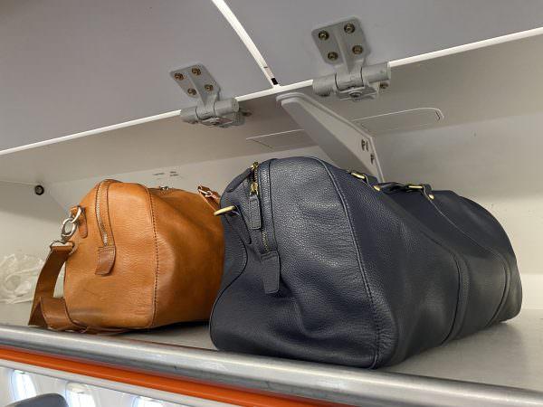 weekend bags in overhead cabin asali